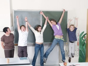 Children in front of chalkboard, excited