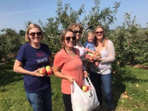Four adults and a baby standing in an apple orchard.