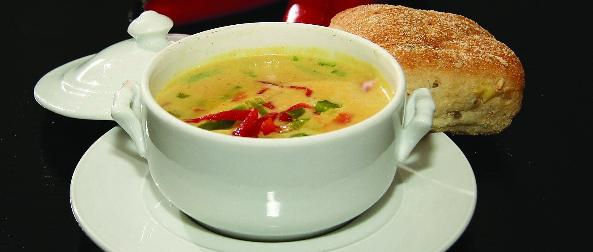 white soup bowl on white plate. Soup bowl filled with yellow colored soup with red and green peppers, and a piece of bread in the background