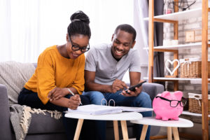 Young Couple Sitting On Sofa Calculating Invoice